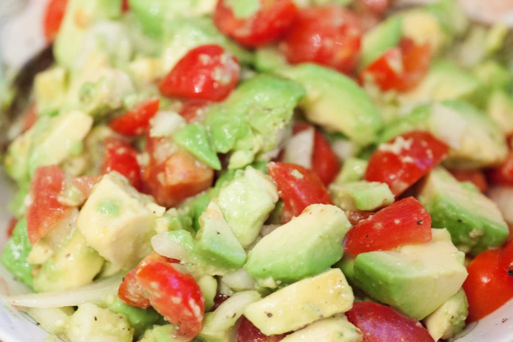 Avocadosalat mit Tomaten wird in einer Schüssel gemischt und mit Zitronensaft Pfeffer und Salz abgeschmeckt.