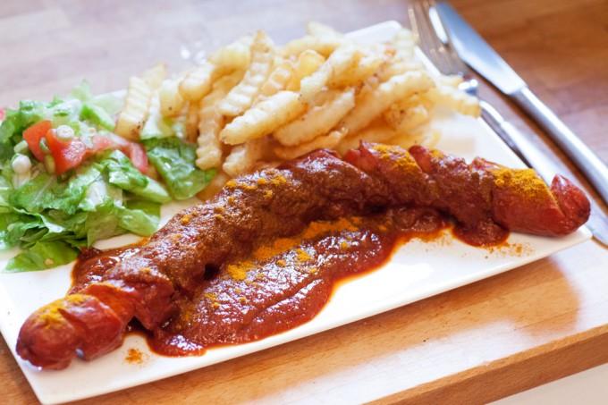 Currywurst mit Pommes und Salat.