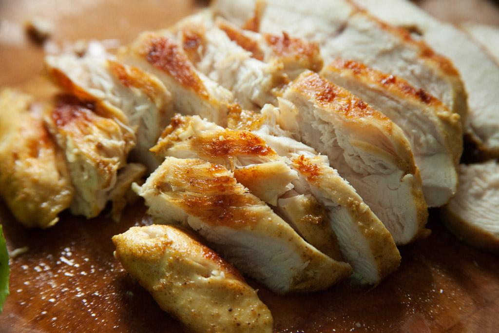 Das Curry-Hühnchen wird in Scheiben geschnitten.
