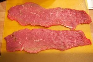 Das Fleisch für die Rinderrouladen wird gesalzen und gepfeffert.
