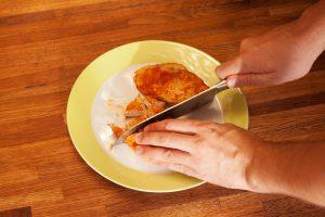 Das Hühnchenfleisch wird in mundgerechte Stücke geschnitten.