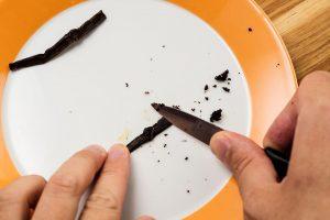 Das Vanillemark wird mit einem Messer aus der Vanilleschote geschabt.