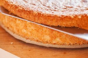 Der Biskuit wird mit einem Brotmesser oder Konditormesser in drei Scheiben geschnitten.