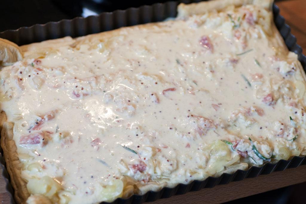 Der Blätterteig wird fuer den Zwiebelkuchen vorgebacken und erst danach belegt.