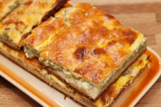 Der Rhabarberkuchen wird in schmale Stücke geschnitten und auf einer Kuchenplatte serviert.