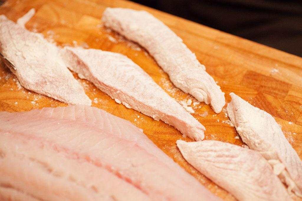 Der Seelachs wird in längliche Stücke geschnitten, gewürtzt und mit Mehl bestäubt.