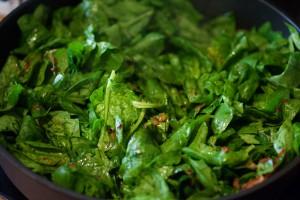 Der frische gewaschene Spinat wird in der Pfanne gedünstet.