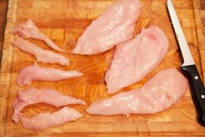 Die Hühnerbrustfilets werden mit einem scharfen Messer von Sehnen und Fett befreit.