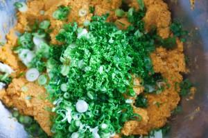Die Masse aus gekochten roten Linsen wird mit frischer Petersilie und Frühlingszwiebeln gemischt.