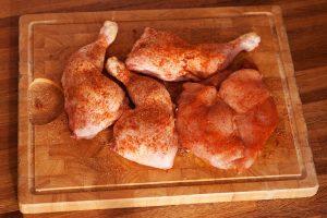 Die Paprikapulver-Chili-Mischung wird auf dem Hühnchen verteilt.