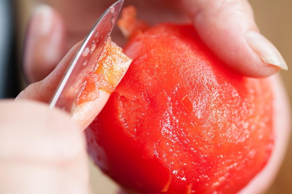 Die Schale der reifen Tomate wird mit einem Küchenmesser abgezogen.