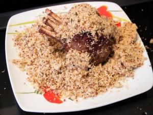 Die Semmelbröselmasse wird an das angebratene Lammfleisch geklebt.