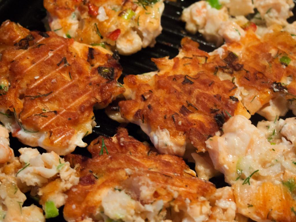Die fertig geformten Fischburger werden in einer Grillpfanne gebraten.