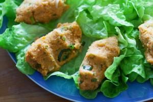 Die fertig geformten Linsenfrikadellen werden auf Salatblätter gelegt.