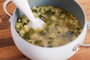 Die fertig gekochte Zucchinisuppe wird mit einem Pürierstab püriert.