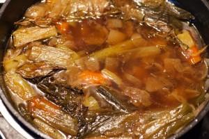 Die groben Bestandteile der Sauce werden ausgesiebt und das Gemüse durch das Sieb gedrückt.