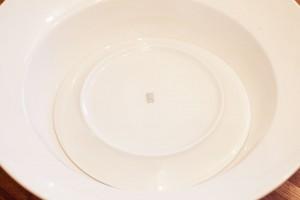 Ein Teller wird mit der Unterseite nach oben in eine große Schüssel gelegt.