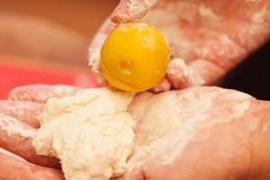 Ein esslöffelgroßes Stück Teig in die bemehlten Hände nehmen.