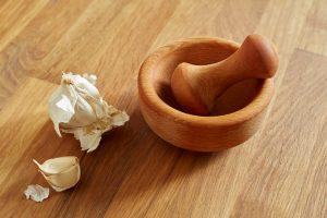 Für den Knoblauchjoghurt wird Knoblauch in einem Mörser zerkleinert.