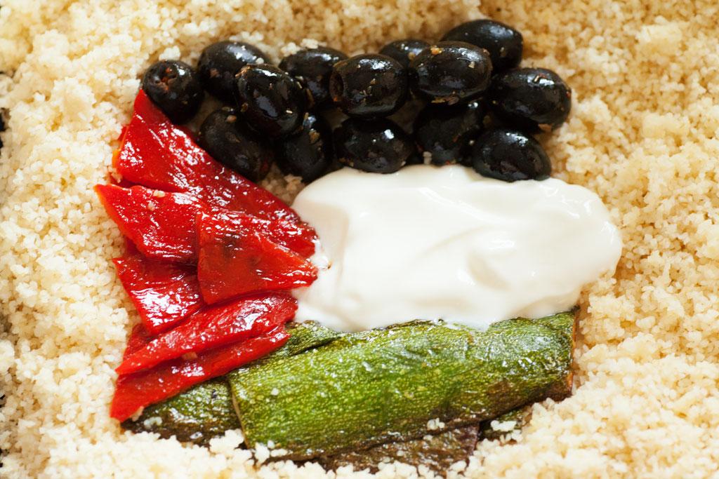 Gebratene Paprika und gebratene Zucchini mit Knoblauchjoghurt, dazu eingelegte schwarze Oliven dekoriert als palästinensische Flagge.
