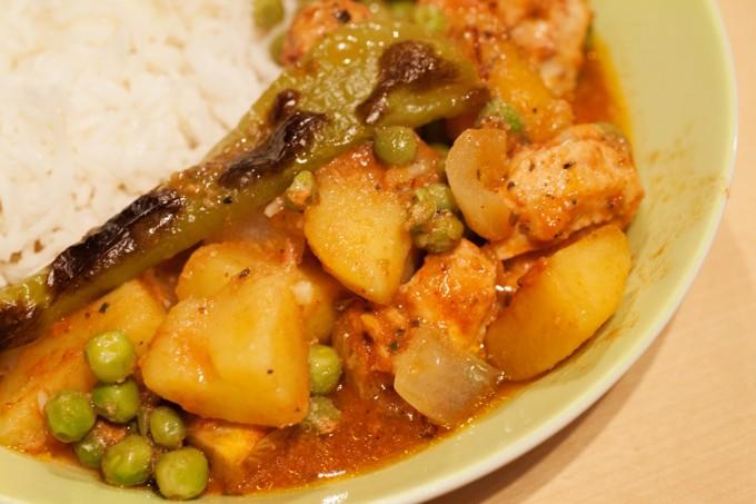 Hühnchenfleisch mit Kartoffeln und Erbsen als Beilage Basmati-Reis.