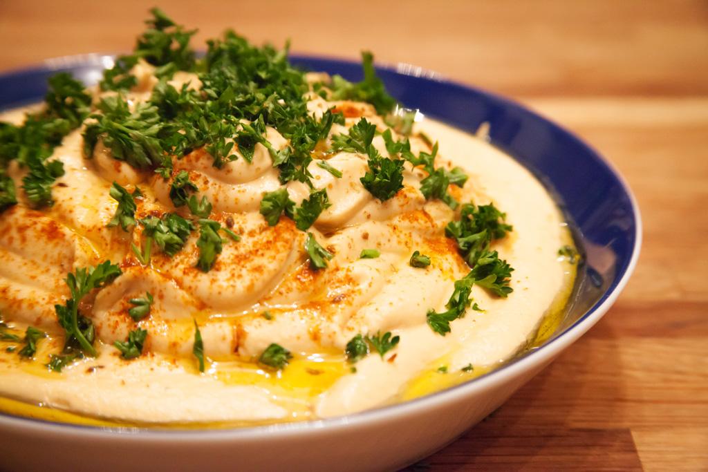 Hummus (Kichererbsenpüree) bestreut mit frischer Petersilie.