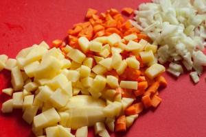 Kartoffeln Möhren und Zwiebeln werden in feine Würfel geschnitten.