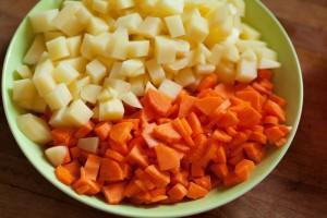 Kartoffeln und Möhren schälen und in kleine Stücke schneiden.