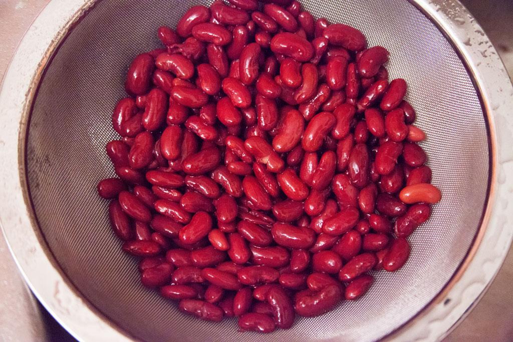 Kidneybohnen aus der Dose werden in ein Küchensieb geschüttet und mit kaltem Wasser abgespült.
