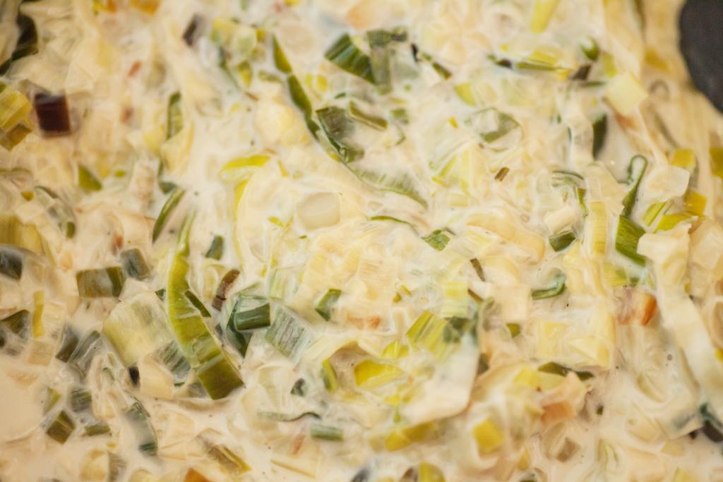 Lauch-Sahne-Sauce mit fein geschnittenem Lauch, je mehr dunkelgrüne Teile verwendet werden desto zwiebeliger und kräftiger wird der Geschmack.