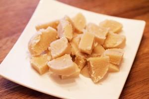 Marzipan Rohmasse wird für die Kokosmakronen in kleinere Stücke geschnitten.