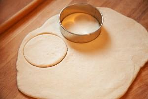 Mit einem kreisrunden Keksausstecher werden die Teigstücke ausgestochen.