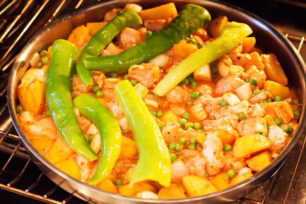 Nach 20 Minuten wird die Alu-Folie entfernt und die scharfen Paprika auf die Hühnchen-Gemüse Mischung gelegt.
