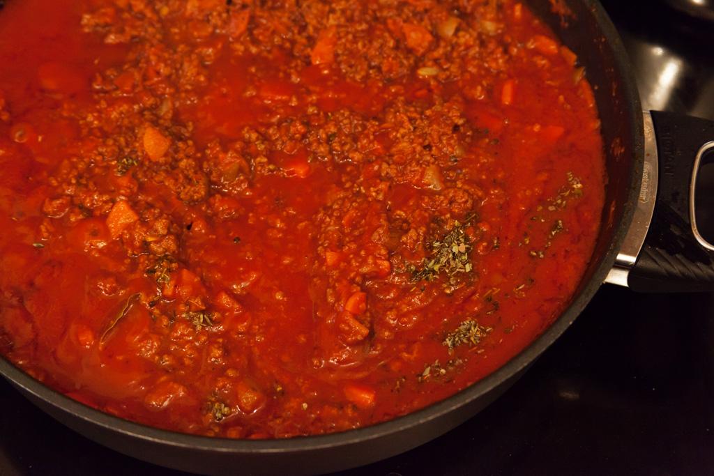 Passierte Tomaten Lorbeerblätter und Italienische Kräuter kommen hinzu.