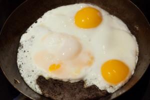 Sobald die Bratkartoffeln fertig sind, werden in der heißen Pfanne die Spiegeleier zubereitet.