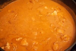 Wenn die Sauce einmal aufgekocht wurde, wird die Temperatur heruntergeregelt und das Hühnchenfleisch kommt wieder in die Pfanne zurück.