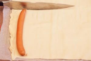 Zugeschnitten wird mit einem scharfen Messer in Länge des einzuwickelnden Würstchens.