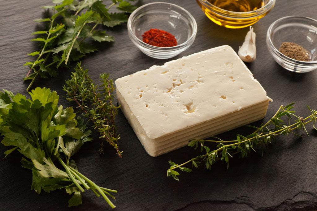 Zutaten für eingelegten Schafskäse mit frischen Kräutern.