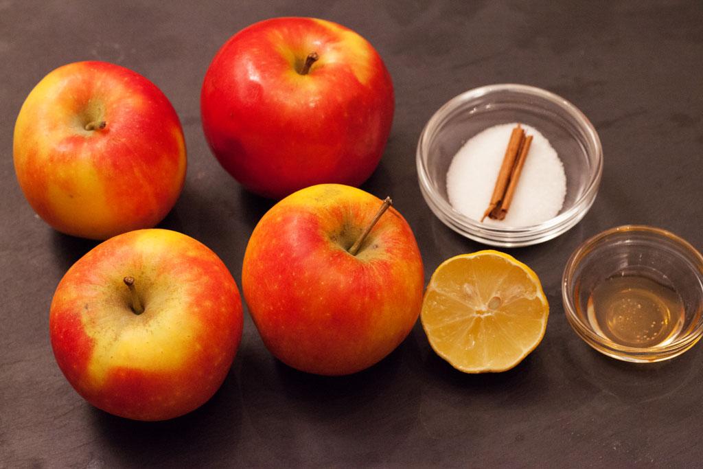 Zutaten für selbstgemachten Apfelmus: Äpfel, Honig, Zucker, Zitronensaft und Zimtstange.