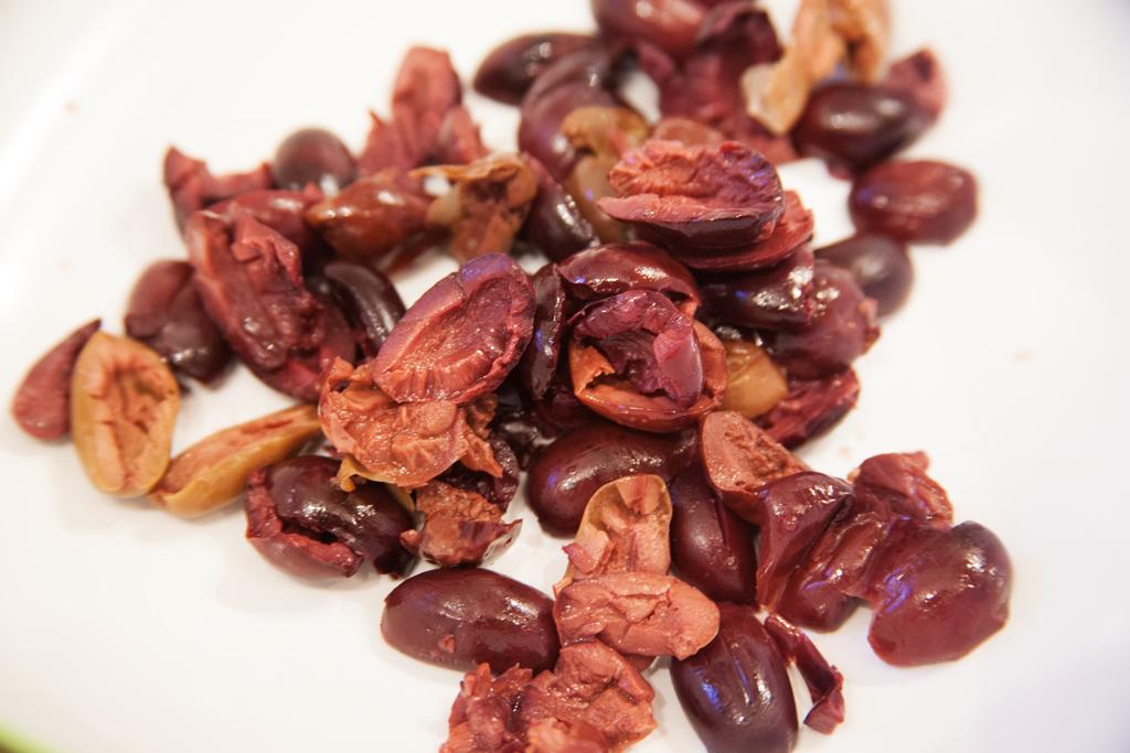 Frisch entkernte und halbierte schwarze Oliven.