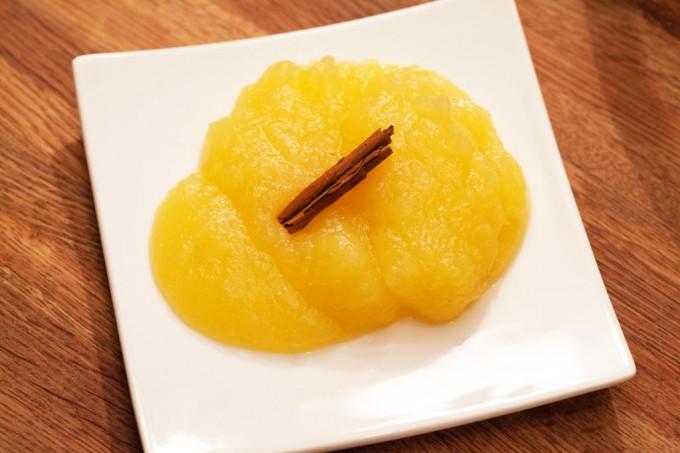 Selbstgemachter Apfelmus mit Zimtstange und Honig.