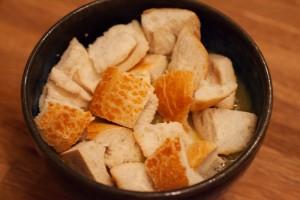 Auf die Suppe werden die Weißbrotstücke gelegt.