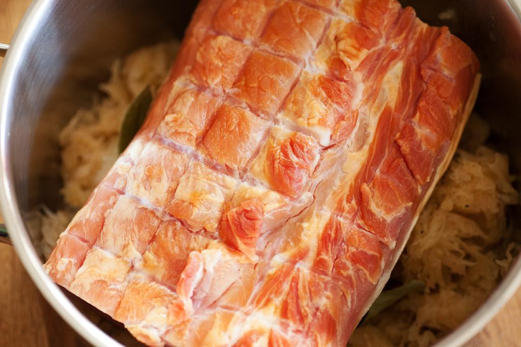 Auf die erste Schicht Sauerkraut wird das Stück Kasseler gelegt.