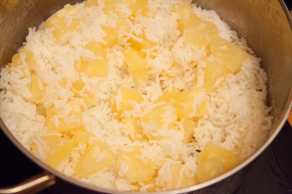 Basmati-Reis wird mit Ananasstücken gemischt.