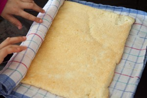 Frisch gebackener Biskuitboden wird in einem Tuch gerollt