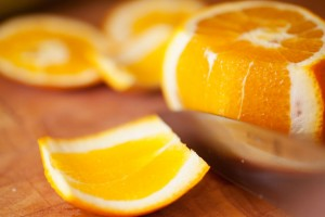 Dann wird die Schale an den Seiten der Orange mit der weißen Schicht abgeschnitten.