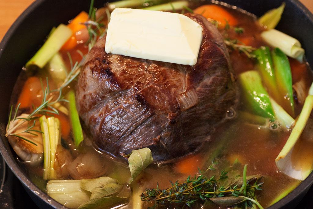 Das Gemüse soll unter Wasser sein, der Rinderschmorbraten mit Butter belegt herausragen.