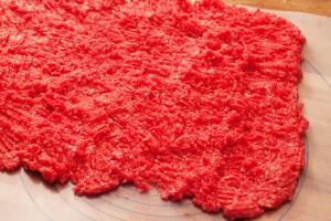 Das Rinderhackfleisch wird mit einer Gabel zu einer dünnen Schicht ausgebreitet.