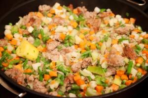 Das Suppengemüse wird im Topf mit Thüringer Mett vermengt.