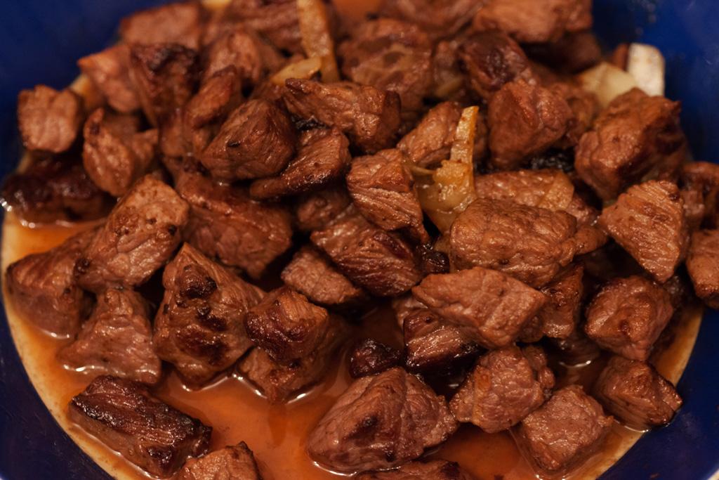 Das gebratene Rindfleisch wird auf einem Teller beiseite gestellt.